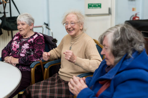 Elderly woman is happily listening to music played in the day care centre