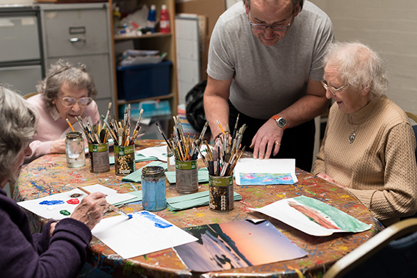 Three service users at Fred Paton Day Care Centre enjoy an art class