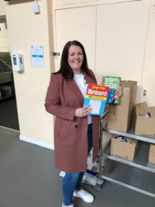 Gillian holds puzzle books donated to charity