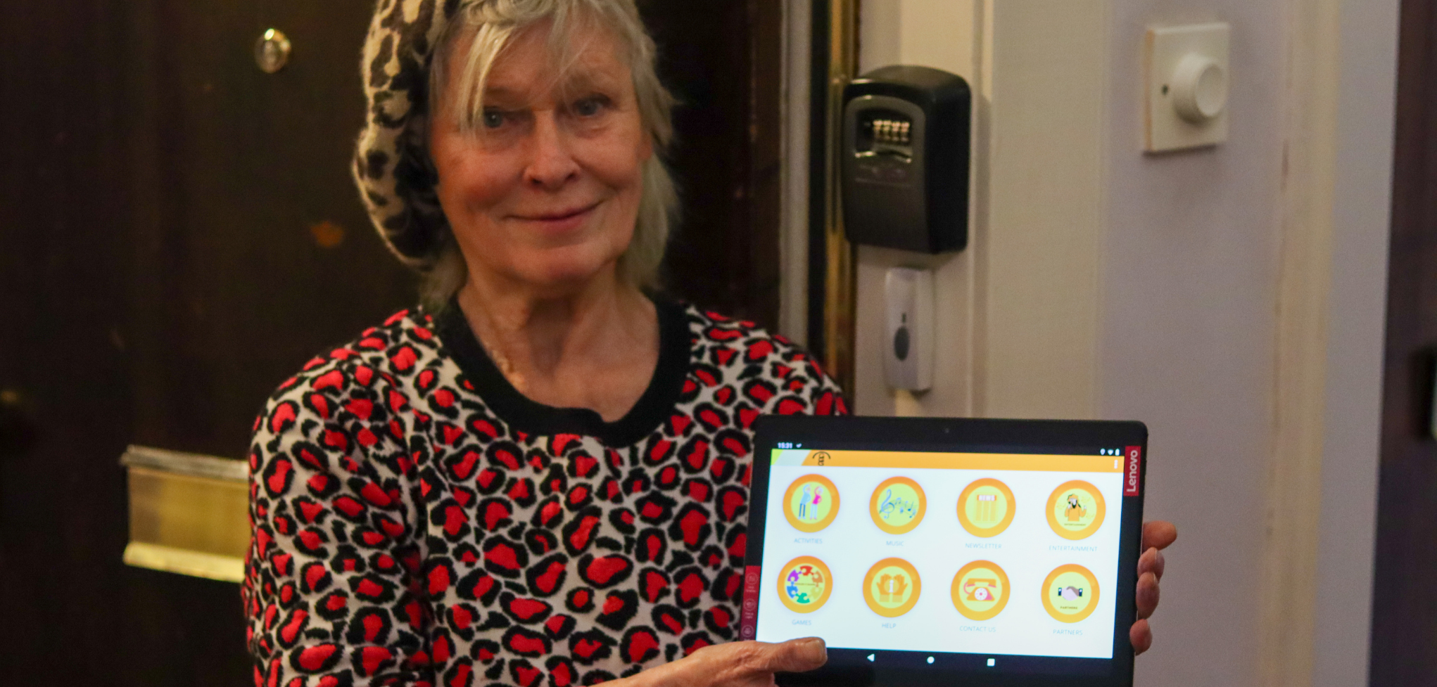 Picture of older adult in front of her door, holding a tablet with icons displayed